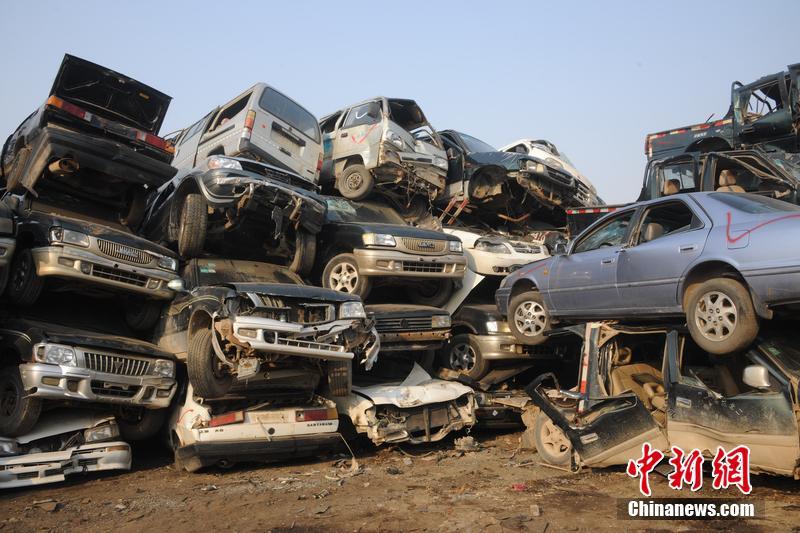 """2015年10月9日消息,山东省东营市,位于东营区科苑一报废汽车回收拆解处,现""""汽车坟场"""",场面十分震撼。现场,数千辆汽车密密麻麻的堆积在拆解场里,几名工人正不紧不慢地处理着这些车子,将它们分割拆解开来。并且将报废汽车内拆卸处发动机、轮胎等部件进行归类。据了解,这些车辆大部分是事故报废车辆。图片来源:CFP视觉中国"""