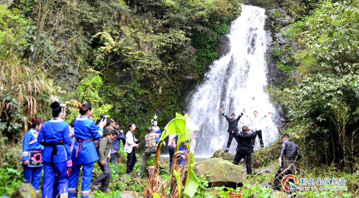 游客在瀑布前留影拍照