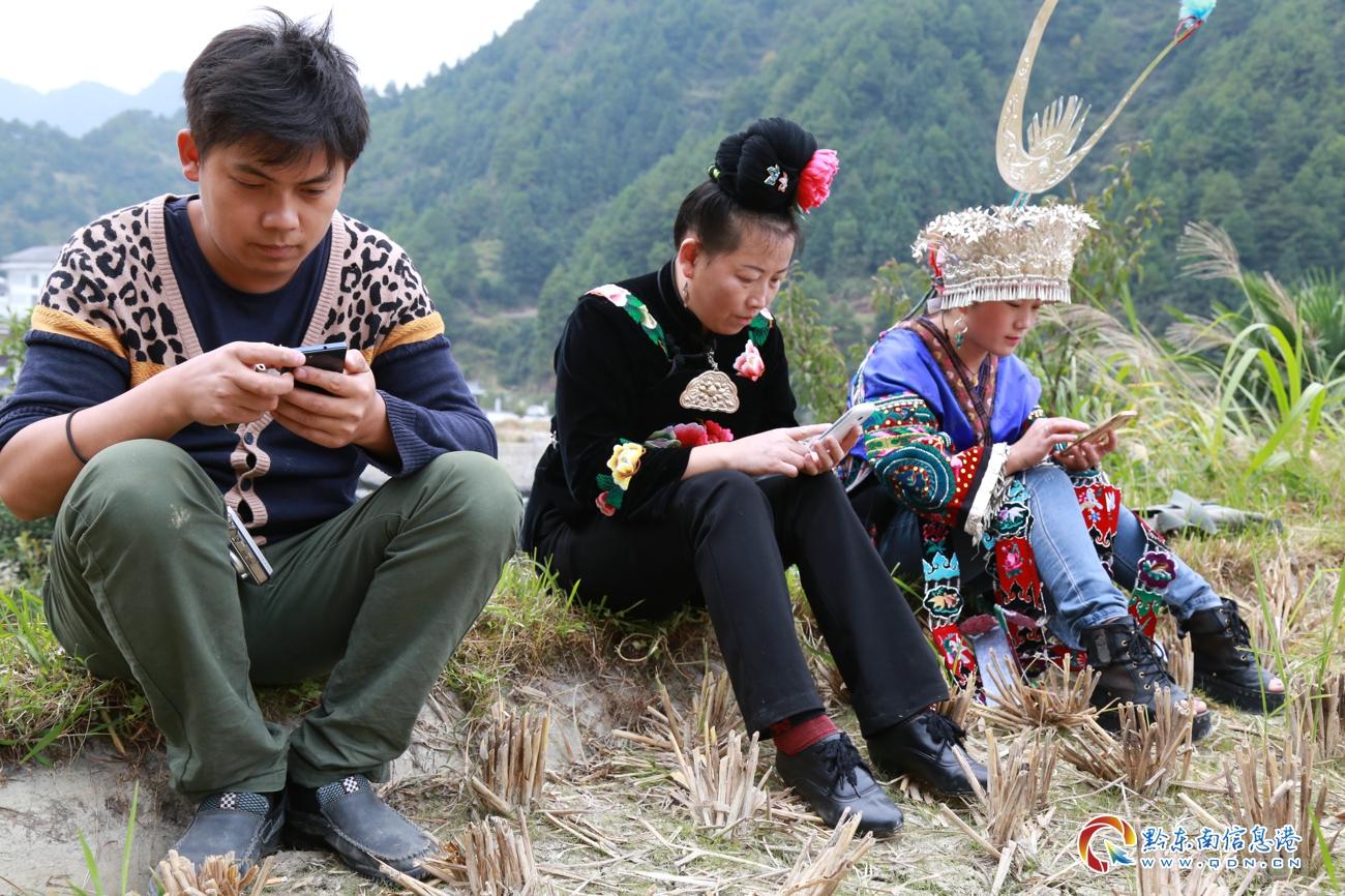 10月10日,贵州雷山国家级芦笙非遗传人莫厌学和他的弟弟莫里学在检修芦笙和校音。图为他的儿子儿媳在等候拿芦笙去参加比赛。李雪摄